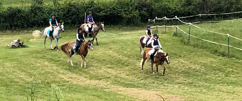 Pony Club members riding in the field